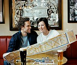 Couple in a Pub Holding a Map