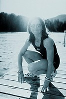 Athletic woman crouching on swimming dock