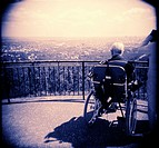 Vignetted image or an elderly male in a wheel chair looking over a town from a high vantage point