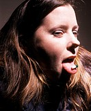 Portrait of female in her 20s with a pill capsule on her tongue
