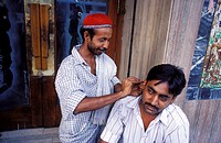 Ear cleaner with a customer. New Delhi, India