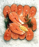 Salmon cutlets with dill and lemon on ice