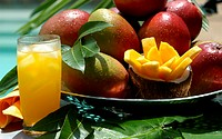 Fresh mangoes, slice of mango and glass of mango juice