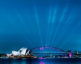Sydney Opera House and Harbour Bridge at dusk with many spotlights on the bridge lighting upwards