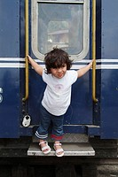 Four years old Indian baby girl holding on to a train. India