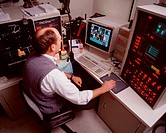 Male technician at work with a FACStarPLUS flow cytometer system, a sophisticated device capable of both cell analysis and cell sorting. Flow cytometr...