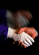 Close-up of hands engaged in a handshake. One belongs to a surgeon and is thus wearing a latex glove. The other hand is bare.