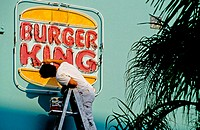 Man repainting a Burger King fast food restaurant facade in the Art Deco district, Miami Beach, Florida. USA