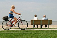 Woman on bike and couple sitting in bench at Lake Erie beach, Maumee Bay State Park. Ohio, USA