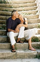 Mature Couple Sit Close to Each Other Side by Side on Stone Steps