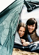 Young Smiling Couple Peek Out From Inside a Tent