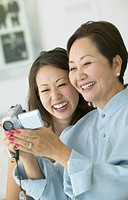 Mother and Daughter Side by Side Holding a Digital Camcorder, Laughing