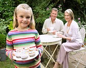 Young Girl in a Garden Holding a Plate Full of Cup Cakes with Two Adults Sat Behind her at a Table, Holding Tea Cups