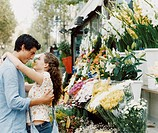 Young Couple Stand Embracing Outside a Florist´s Shop