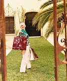 Senior Woman Stands on the Lawn Outside Her Mansion Carrying Shopping Bags