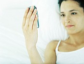 Woman lying on back on bed, looking at cell phone