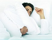 Man lying in bed on side holding pillow