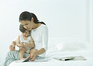 Woman sitting on edge of bed with little girl on lap, looking down at agenda