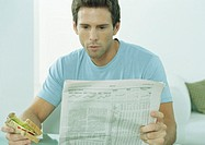 Young man reading newspaper and eating sandwich (thumbnail)