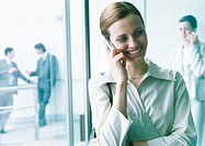 Businesswoman talking on cell phone, businesspeople in background