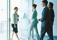 Businesspeople entering and exiting through glass doors
