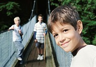 Close-Up of a Young Boy on a Rope Bridge, His Two Friends Standing in the Background