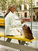 Businesswoman Sits at Bus Stop Using Her Mobile Phone