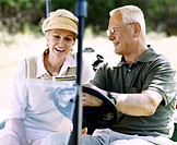 Senior Couple Sitting in a Golf Buggy Comparing Scores