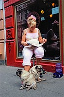 Hairdresser sitting in front of her shop, reading a magazine with two pug dogs. Glashuttenstrasse. Karolinenviertel. Hamburg. Germany.