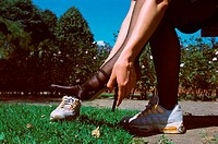 Woman changing shoes in park