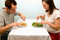 Couple eating contrasting meals