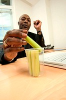 Businessman eating celery