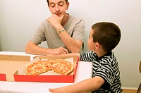 Father and son eating pizza