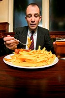 Businessman eating plate of french fries