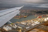 Wing of aircraft flying over Barcelona harbour shortly after rainstorm. Spain