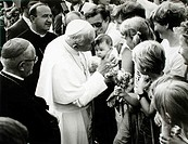 The Pope blesses a baby during his visit to Switzerland in 1985
