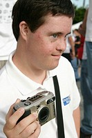 Teenager with Down syndrom with digital camera. Bayfront Park. Miami. Florida. USA.