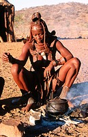 Himba wife at the fire place. Kaokoveld. Namibia