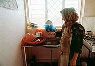 Kurdish woman in her new kitchen in the village, Kurdistan, Iraq 2004