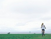 Woman riding bicycle on grass, sea and overcast sky in background