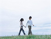 Young man and woman walking on grass holding hands