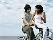Young man sitting on bicycle, young woman sitting on bicycle basket looking over shoulder at young man