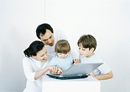 Boy and little girl with parents using laptop together
