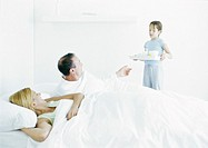Girl bringing parents breakfast in bed