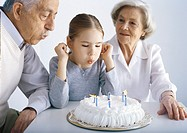 Grandparents and girl sitting at table blowing out candles on cake