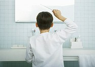 Boy combing hair in mirror, rear view