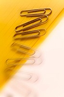 Paper clips falling off yellow notepad