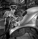 A rivetter uses a pneumatic drill to rivet a steel car frame at the Brixton workshops of Reynolds engineering.Photograph by Walter Nurnberg, who trans...