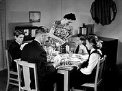A photograph of a family at breakfast, taken by Photographic Advertising Limited in about 1948.  Father reads the post while mother stands to pour a d...