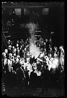 A photograph of Professor Alexander Oliver Rankine producing a synthetic snowstorm during a lecture to an audience of school children, taken by James ...